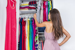 Woman choosing clothes to wear in clothing closet. Home woman choosing her fashion outfit in dressing room. Woman in bedroom walk-in organized closet looking at Stock Image