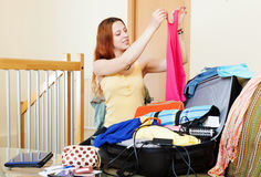 Woman choosing clothes for vacation  at home Royalty Free Stock Images