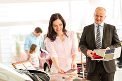 Woman choosing the color of family car. Young wife choosing the color of family car Stock Photography