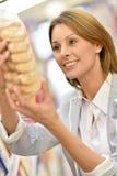 Woman choosing cookies to buy Stock Image