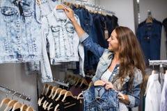 Woman choosing denim jacket in shop Stock Photo