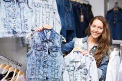 Woman choosing denim jacket in shop Stock Photography