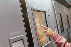 Woman choosing the destination on subway train ticket machine. Transportation concept stock images
