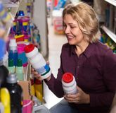 Woman choosing detergent. Mature blonde woman choosing detergent in laundry section of supermarket Royalty Free Stock Images