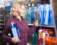 Woman choosing detergent Royalty Free Stock Image