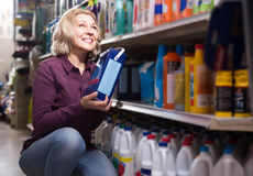 Woman choosing detergent Stock Images