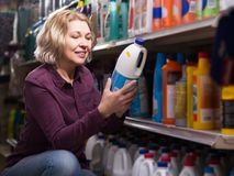 Woman choosing detergent. Mature woman choosing detergent in laundry section of supermarket Royalty Free Stock Image
