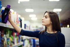 Woman choosing detergent in supermarket Royalty Free Stock Images