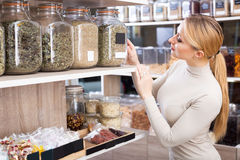 Woman choosing dried herbs. Smiling young blond woman choosing dried herbs sold by weight in organic shop Stock Photography