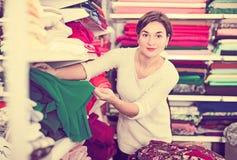 Woman choosing fabric. Girl customer looking for beautiful fabric in drapery shop Stock Image