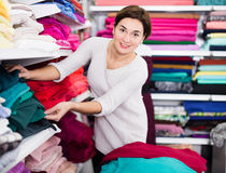 Woman choosing fabric. Girl customer looking for beautiful fabric in drapery shop Royalty Free Stock Photography