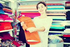 Woman choosing fabric. Young woman choosing interesting fabric in drapery shop Stock Image