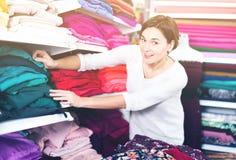 Woman choosing fabric. Young woman choosing interesting fabric in drapery shop Stock Images