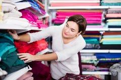 Woman choosing fabric. Young woman choosing interesting fabric in drapery shop Stock Photos