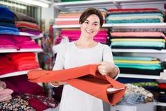 Woman choosing fabric. Young woman choosing interesting fabric in drapery shop Royalty Free Stock Photo