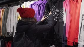 Woman choosing fashion clothes in retail shop in the city mall. Shopping concept. Slow motion stock video footage