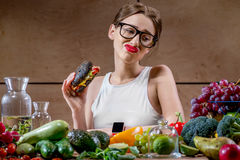 Woman choosing between fast food and healthy vegetables, fruits Royalty Free Stock Photo