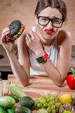 Woman choosing between fast food and healthy vegetables, fruits Stock Photo