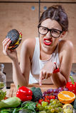 Woman choosing between fast food and healthy vegetables, fruits Stock Photography