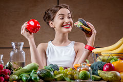 Woman choosing between fast food and healthy vegetables, fruits Royalty Free Stock Photos