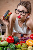Woman choosing between fast food and healthy vegetables, fruits Royalty Free Stock Images
