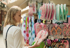 Woman choosing flip-flops. Stock Photos
