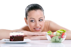 Woman choosing  food. Dieting concept,  beautiful young woman choosing between healthy food and tasty cakes Royalty Free Stock Photography