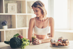 Woman choosing food. Beautiful young sportswoman is choosing between the plate of vegetables and the plate of cakes in kitchen at home Royalty Free Stock Images