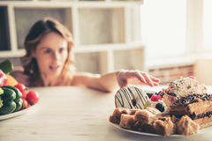 Woman choosing food. Beautiful young sportswoman is choosing between the plate of vegetables and the plate of cakes in kitchen at home Stock Images