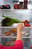 Woman choosing food from refrigerator. Female hand choosing food from interior of refrigerator Royalty Free Stock Images