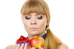 Woman choosing fruit or cake make dietary choice Royalty Free Stock Image