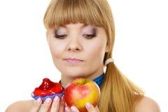 Woman choosing fruit or cake make dietary choice Stock Photos