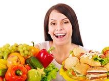 Woman choosing between fruit and hamburger. Royalty Free Stock Images