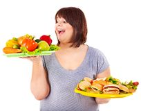Woman choosing between fruit and hamburger. Royalty Free Stock Photos