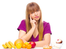 Woman choosing between fruit and sweets Royalty Free Stock Photography