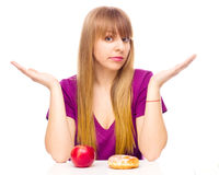 Woman choosing between fruit and sweets Royalty Free Stock Image