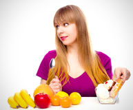 Woman choosing between fruit and sweets Stock Photo