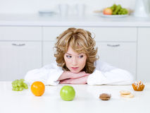 Woman choosing between fruits and cakes Royalty Free Stock Photo