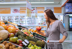 Woman choosing fruits in the shop Stock Photos
