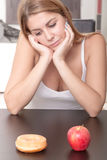 Woman choosing between Fruits and Sweets Stock Photo