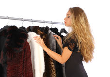 Woman choosing a fur coat Stock Photos