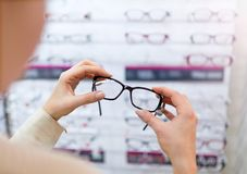 Woman choosing glasses in optician store Royalty Free Stock Images