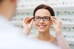 Woman choosing glasses at optics store Stock Images
