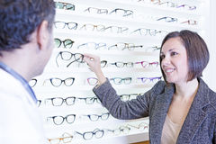 Woman choosing glasses. Smiling young women asking for advice to the optician and choosing glasses at the optical store Stock Image