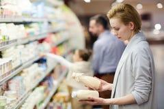 Woman Choosing Good Milk. Side view portrait of blond women choosing milk in dairy product department stock images