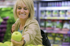 Woman choosing green apple from display in supermarket, smiling (differential focus) Stock Image