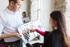 Woman choosing hair color from palette at salon Stock Images