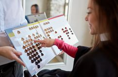 Woman choosing hair color from palette at salon. Beauty, hair dyeing and people concept - happy young women with hairdresser choosing hair color from palette Royalty Free Stock Photos