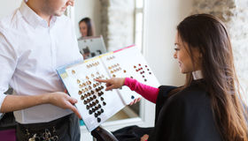 Woman choosing hair color from palette at salon Royalty Free Stock Photos