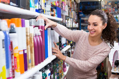 Woman choosing hairspray in supermarket Royalty Free Stock Photography